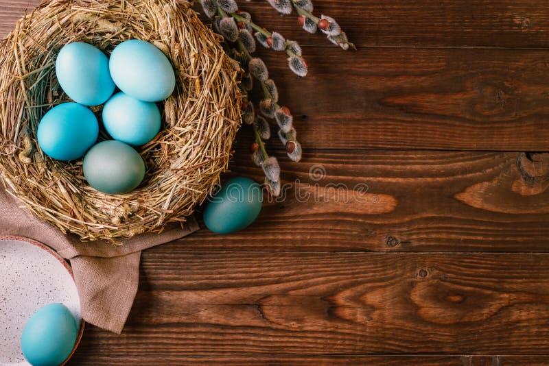 Kulöra påskägg för turkos i rede på tappningträbakgrund arkivfoto