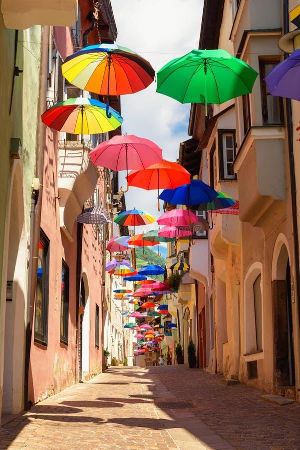 Kulöra paraplyer dekorerar gränden i gammal stad i Chiusa Italien royaltyfri bild
