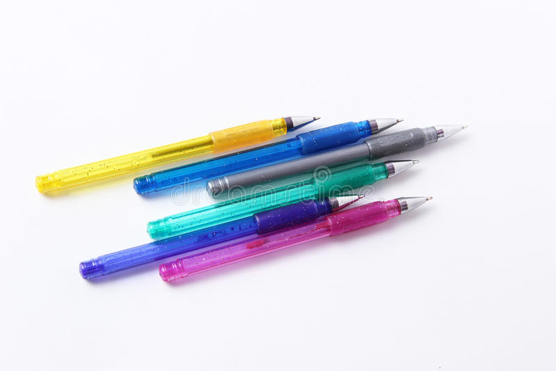 Kulöra pennor på vit bakgrund arkivfoto