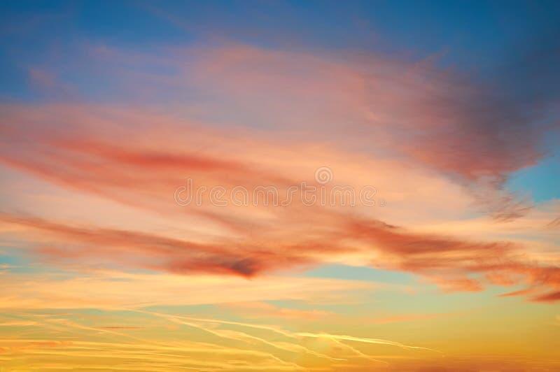 Kulöra porösa moln på solnedgången mot blå himmel dramatisk sky royaltyfri foto