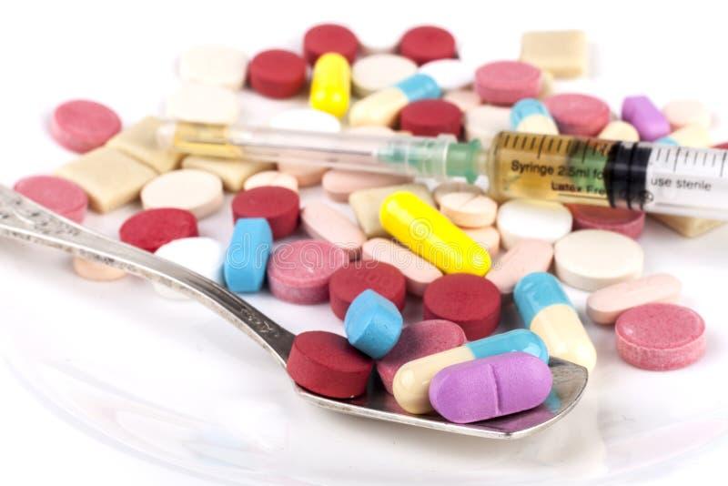 Kulöra preventivpillerar i sked arkivbilder