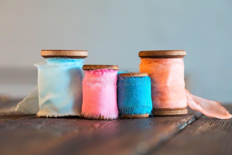 Kulöra spolar av kulöra bomullsband på träyttersida arkivfoton