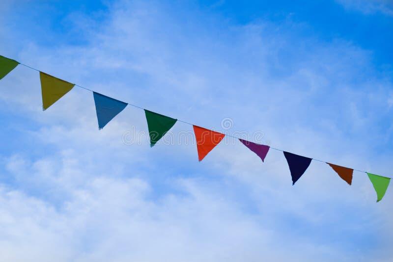 Kulöra triangulära flaggor på ljus bakgrund för blå himmel arkivbild
