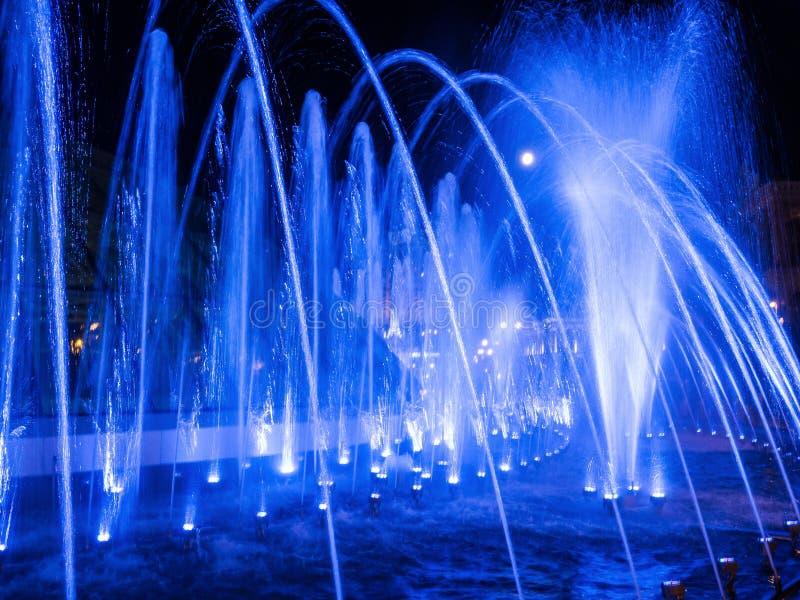 Kulöra vattenstrålar i springbrunnen på natten med fullmånen royaltyfri foto