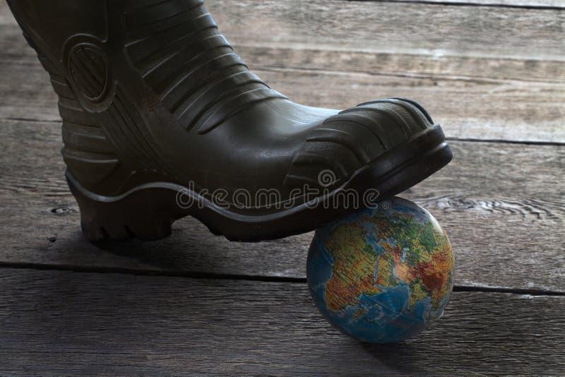 Kula ziemska pod stopą w gumowym bucie fotografia stock