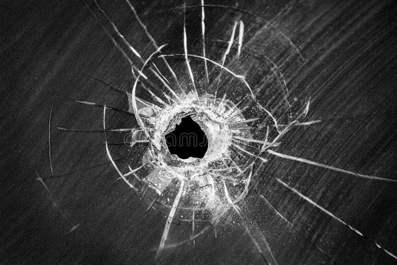 Kulan sköt det spruckna hålet på brutet fönsterexponeringsglas royaltyfria bilder