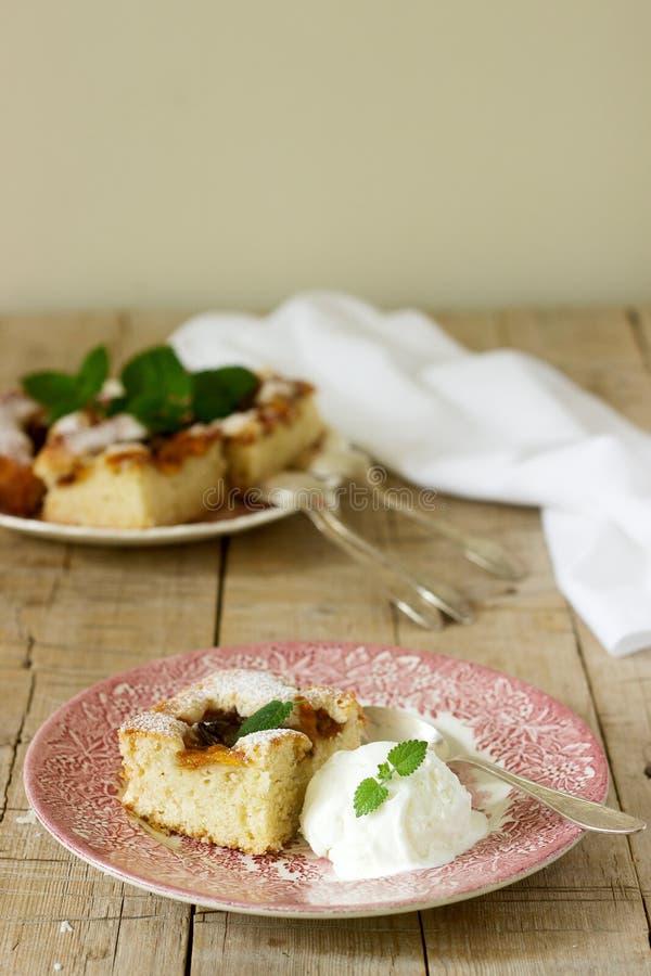 Kulebiak z śliwkami i brzoskwiniami słuzyć z balsamów liśćmi, waniliowej lody piłki, cytryny i obraz royalty free