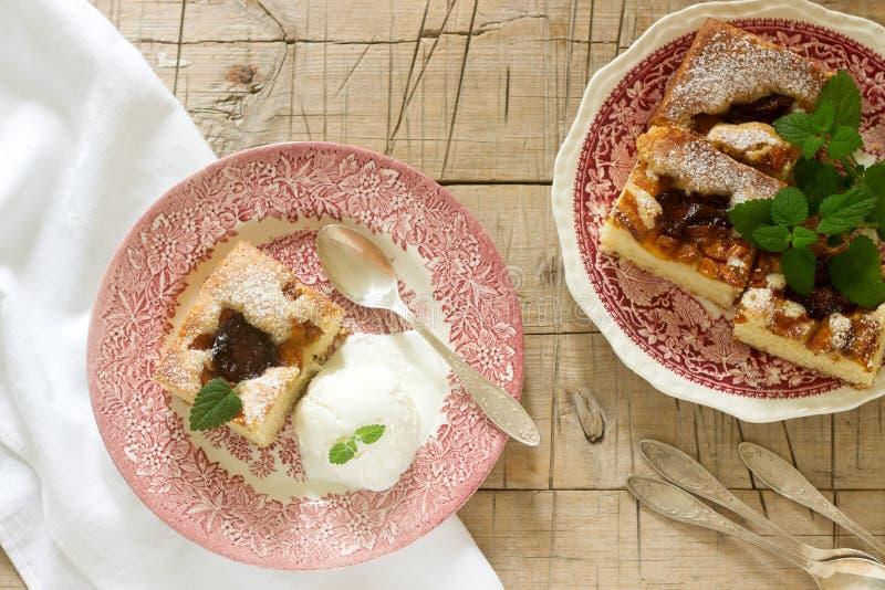Kulebiak z śliwkami i brzoskwiniami słuzyć z balsamów liśćmi, waniliowej lody piłki, cytryny i zdjęcia royalty free