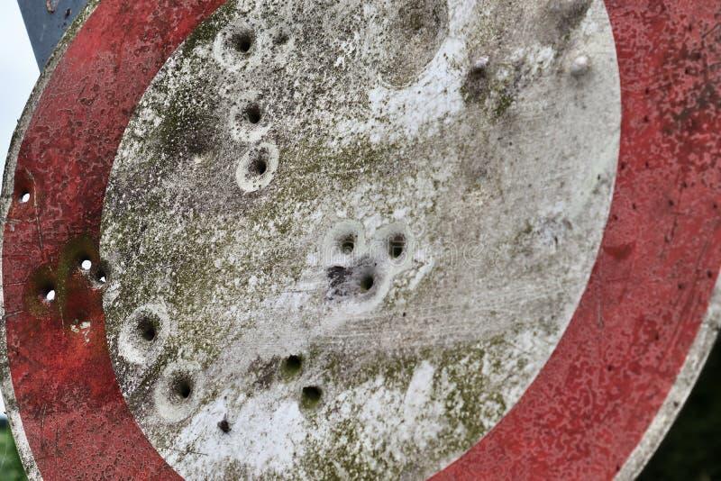 Kulhål från vapenskytteövningar i ett tyskt trafiktecken arkivbilder