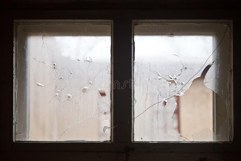 Kulhål på brutet fönsterexponeringsglas arkivfoto