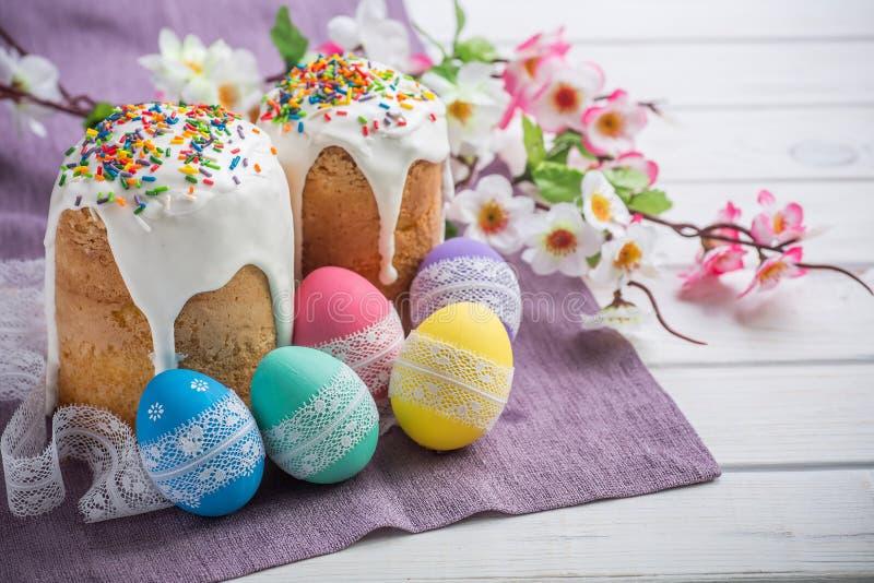 Kulich, traditioneller russischer Ukrainer-Ostern-Kuchen mit Zuckerglasur und farbigen Eiern mit Spitzeband auf weißem hölzernem  lizenzfreie stockfotos