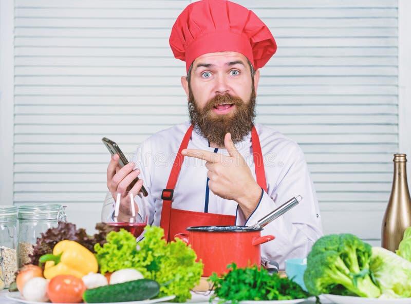 Kulinarische Show der Chef Smartphone-Uhr Kochschule Hippie im Hut und Schutzblech, die wie den Koch on-line lernen kulinarisch lizenzfreie stockfotografie