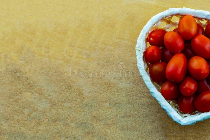 Kulinarischer Entwurf ein Bündel Kirschtomaten-Minigemüse in einem weißen Korb auf einem hölzernen Hintergrundkopienraum stockfotografie