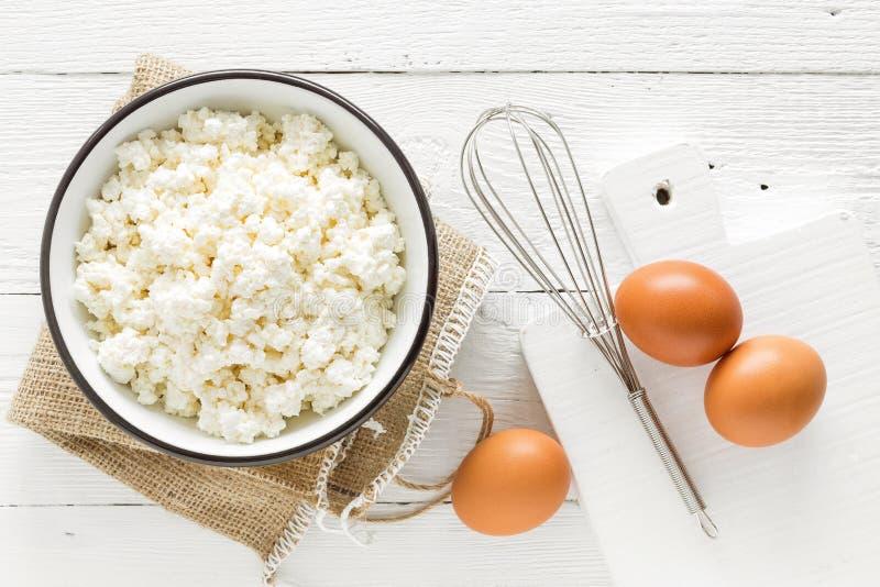 Kulinarisk bakgrund med ingredienser för att laga mat, keso som bakar mjöl, socker och ägg på den vita trälantliga tabellen royaltyfri foto