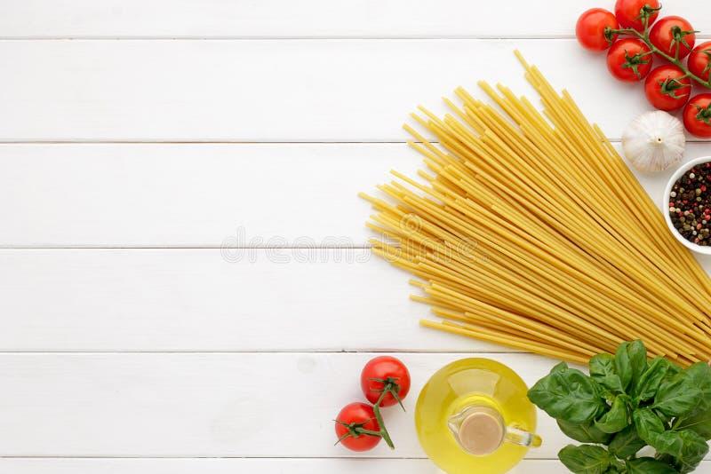 Kulinarisk bakgrund med ingredienser för italiensk maträtt: pastabucatini med grönsaker på vit träbakgrund royaltyfria foton