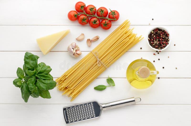 Kulinarisk bakgrund med ingredienser för recept av den italienska pastabucatinien på vit träbakgrund arkivfoton
