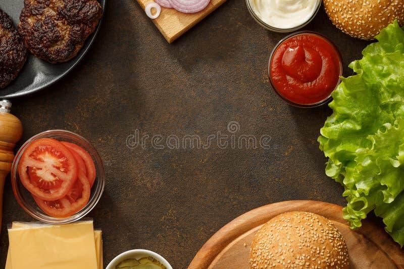 Kulinarisk bakgrund med nya ingredienser för hemlagade hamburgare på den bruna stentabellen arkivbild