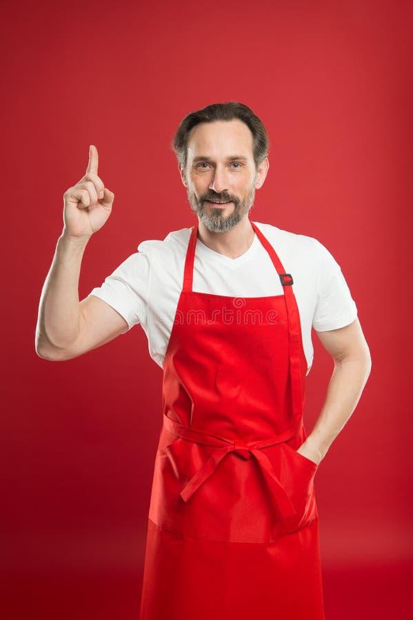 Kulinarisk magi Laga mat med bakgrund för förklädet för skägget och för mustaschen bärande röd Mogen kock för man som poserar lag arkivbild