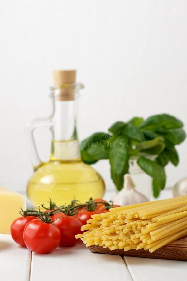 Kulinarisk stilleben med den torra pastabucatinien, nya tomater och basilika, flaska av olja på ljus bakgrund arkivbilder