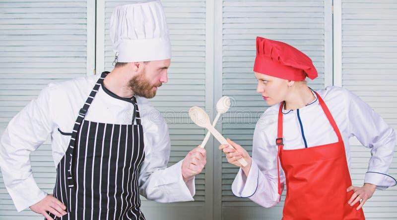 Kulinarisk strid av tv? kockar Par konkurrerar i kulinariska konster K?kregler Kulinariskt stridbegrepp Kvinna och upps?kt royaltyfri bild