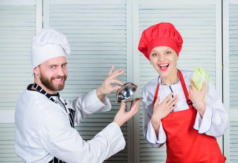 Kulinariskt överraskningbegrepp Läckert mål Kulinariskt showlag för kvinna och för skäggig man Ultimat laga mat utmaning arkivfoto