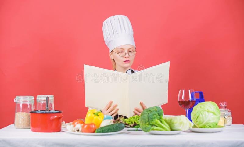 Kulinariskt skolabegrepp Kvinnlign i hatt och f?rkl?de vet allt om kulinariska konster Kulinarisk expert Kvinnakock arkivbilder