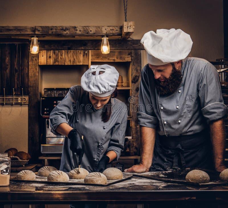Kulinarna mistrz klasa w piekarni Szef kuchni z jego asystentem pokazuje przygotowywać próbki wypiekowy test w kuchni zdjęcie royalty free