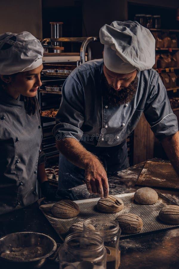 Kulinarna mistrz klasa w piekarni Szef kuchni z jego asystentem pokazuje przygotowywać próbki wypiekowy test w kuchni zdjęcia stock