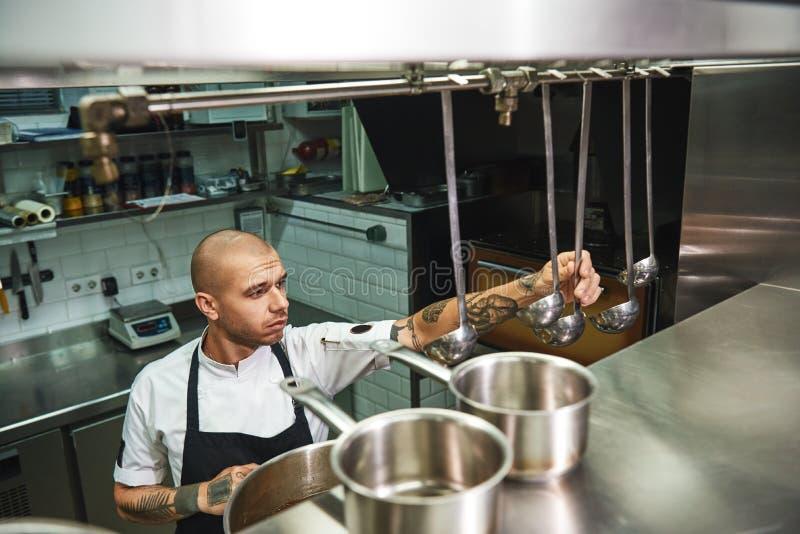 Kulinarna polewka Młody męski szef kuchni wybiera kopyść dla jego sławnej polewki w fartuchu podczas gdy stojący w restauracyjnej zdjęcia stock