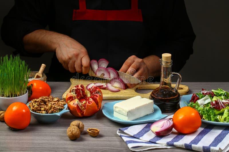 Kulinarna sałatka z persimmon szef kuchni rękami, kroka proces na kuchni na czarnym tło kopii teksta przepisie zdjęcie stock
