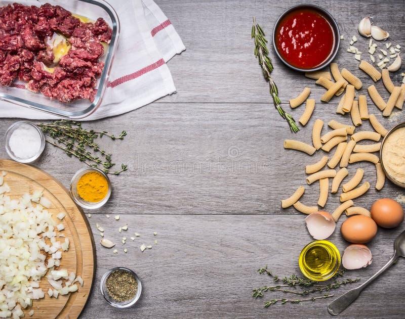 Kulinarnego pojęcia surowa minced mięsna wołowina z jajecznymi ziele przyprawia sól pokrajać czerwonej cebuli kumberlandu penne j fotografia stock