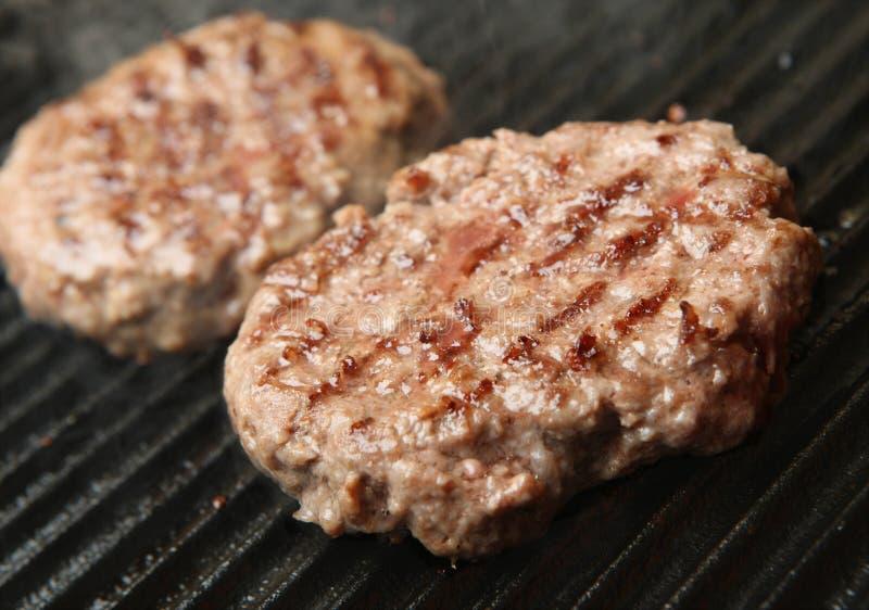 Kulinarni wołowina hamburgery na Griddle obraz stock
