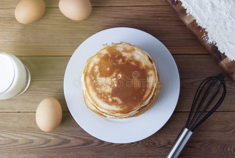 Kulinarny blin na drewnianych tło odgórnego widoku składnikach dla robić blinowi: mleko, jajka, mąka obraz royalty free
