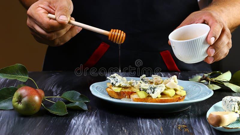 Kulinarny bruschetta z bonkretami, serem i miodem na całości adry, piec chleb - na ciemnego czerni tle fotografia stock