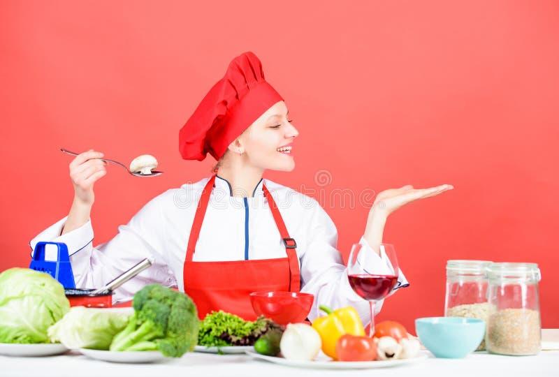 Kulinarny posi?ek Kobieta szefa kuchni pr?by smak je jedzenie t Dziewczyna przy kuchennym sto?em Kulinarny jedzenie i zdjęcie royalty free