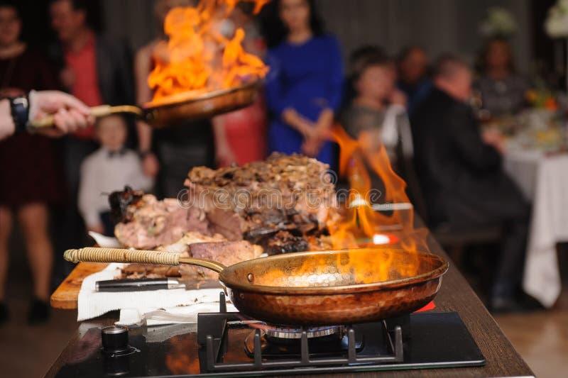 Kulinarny przedstawienie, szefów kuchni kucharzi, smaży mięso w smaży niecce z ogieniem zdjęcie stock