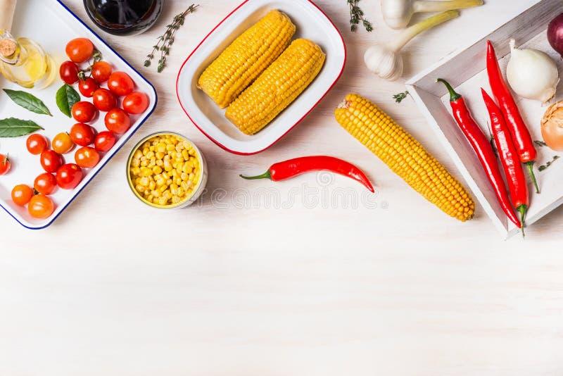 Kulinarny przygotowanie z ucho konserwować i gotująca kukurudza kukurudza, i składniki dla jarskiego naczynia na białych drewnian fotografia stock