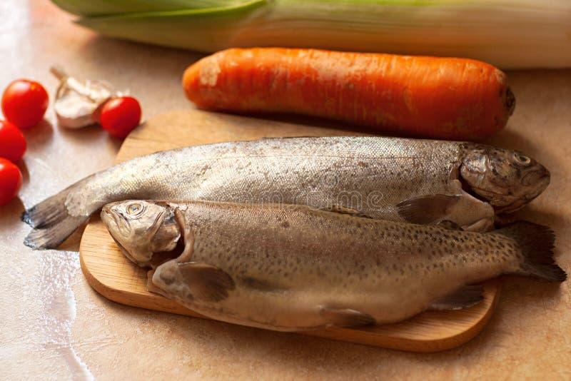 Kulinarny rybi gość restauracji Lay surowy denny bas z warzywami nad nieociosanym tłem, odgórny widok obrazy stock