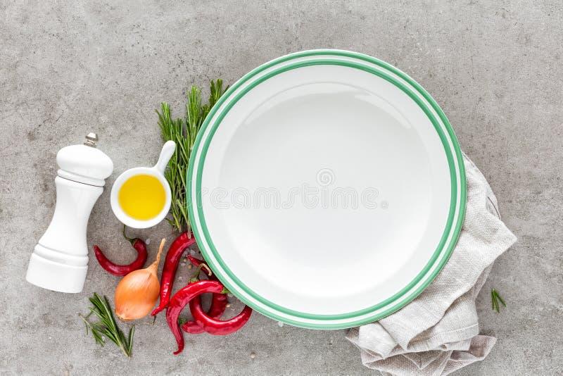 Kulinarny tło z pustym talerzem i przestrzeń dla teksta, mieszkanie nieatutowego składu olej, chili pieprzy, rozmarynów, cebuli i zdjęcie stock