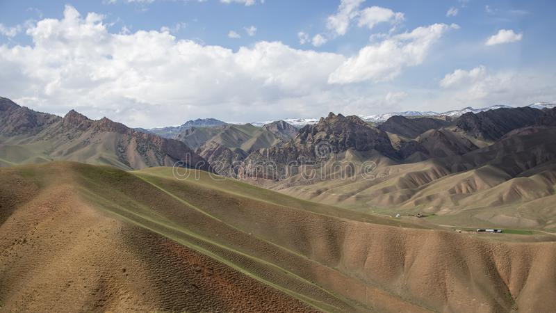 Kullar som täckas med ungt gräs mot himlen och dekorkade bergmaxima Resor kyrgyzstan royaltyfri fotografi