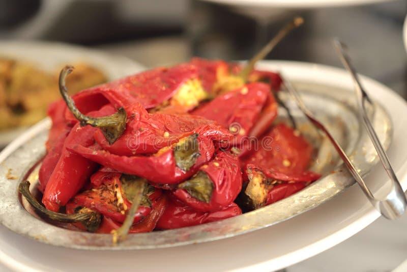 Kulle av röda grillade peppar på en vit platta royaltyfria bilder
