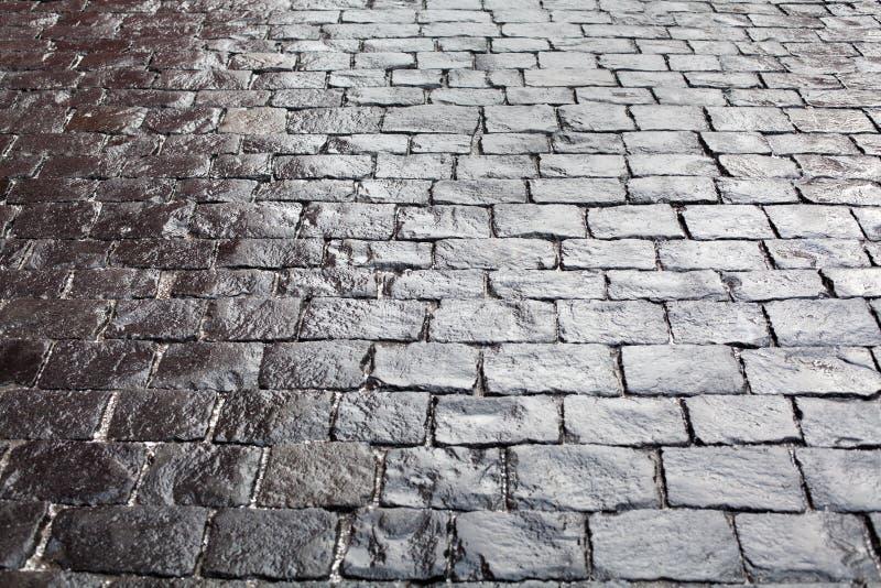 Kullersten på trottoarbakgrund, grå eller svart färg för stentrottoartextur, vått slut för bästa sikt för modell för tegelstenväg arkivfoton