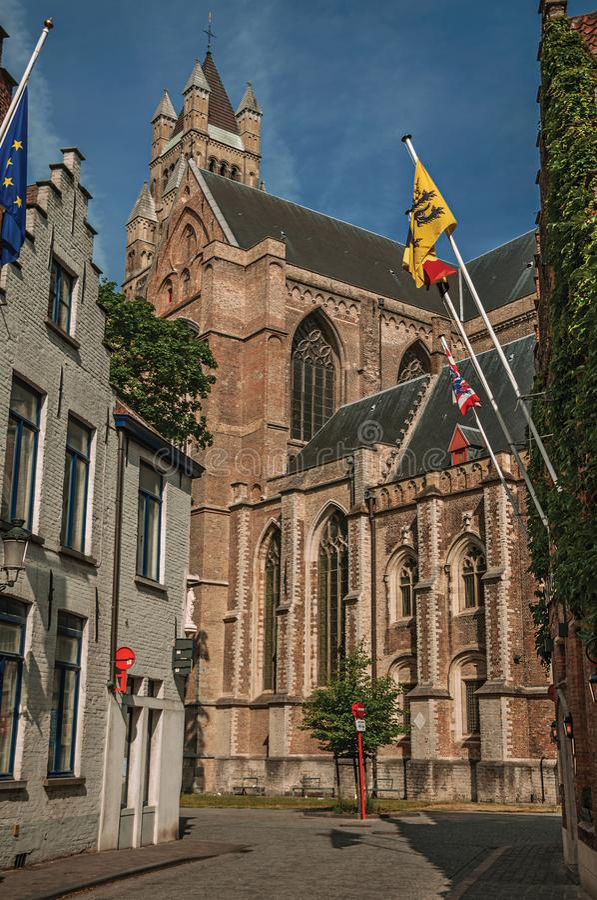 Kullerstengatan med tegelstenhus och kyrkan i Flanders's utformar och flaggor på Bruges royaltyfri foto