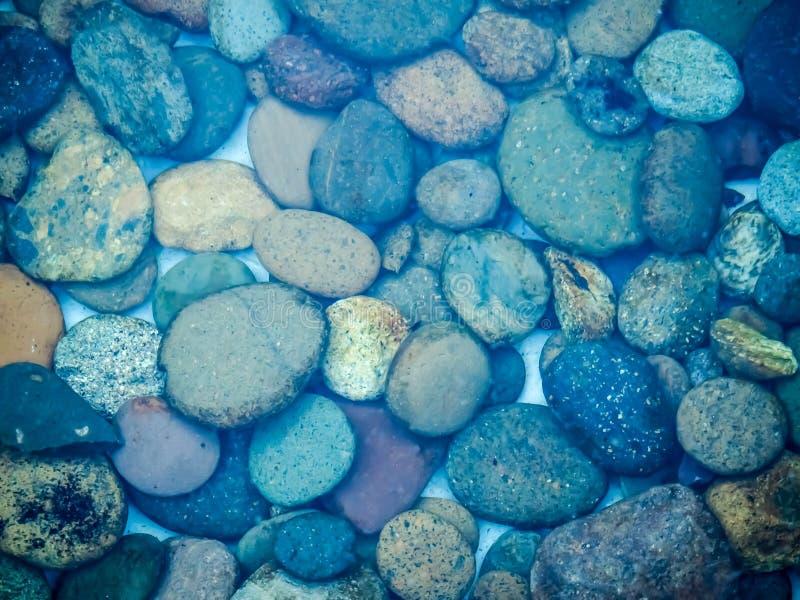 Kullerstenstenar under blått vatten royaltyfri fotografi