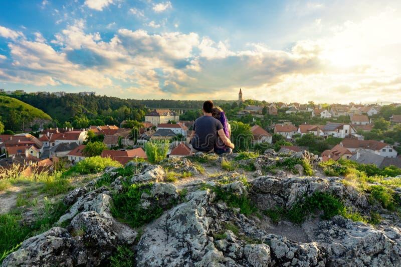 Kulleträdgården i mitt av den gamla staden Veszprem, Ungern med ett par som sitter över staden på klippan som tycker om royaltyfria bilder