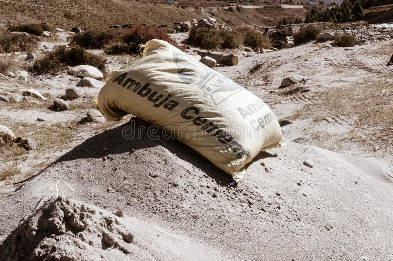 Kullu District, Manali Tehsil, Himachal Pradesh, South Asia, India, October 2019- An open bag of dry Ambuja cement packet placed. On industrial road stock image