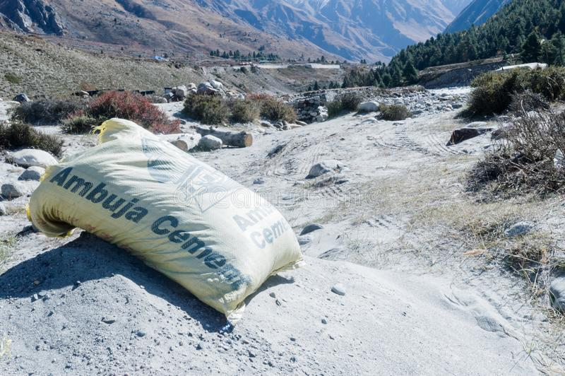 Kullu District, Manali Tehsil, Himachal Pradesh, South Asia, India, October 2019- An open bag of dry Ambuja cement packet placed. On industrial road royalty free stock photography