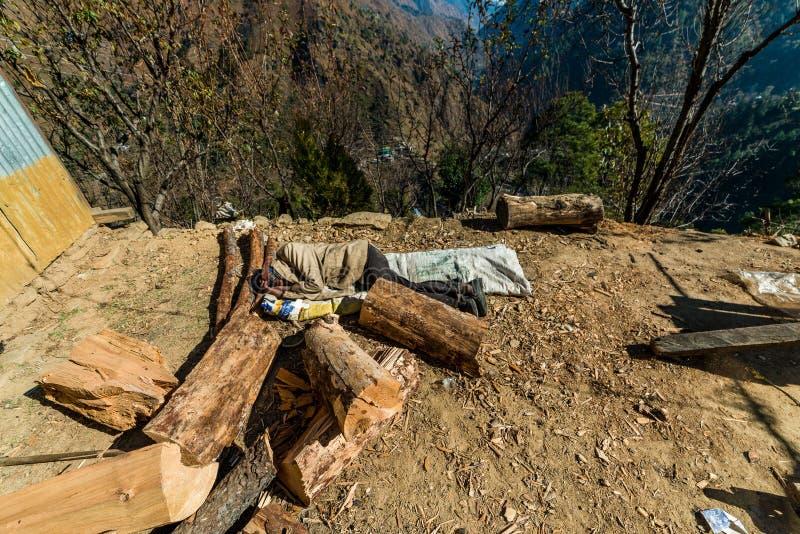 Kullu, Himachal Pradesh, India - December 03, 2018 : elderly carpenter sleeping on ground in himalayas. Kullu, Himachal Pradesh, India - December 03, 2018 royalty free stock image