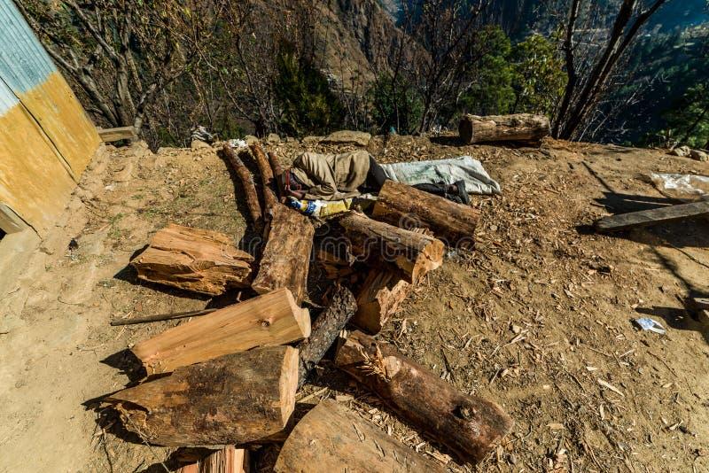 Kullu, Himachal Pradesh, India - December 03, 2018 : elderly carpenter sleeping on ground in himalayas. Kullu, Himachal Pradesh, India - December 03, 2018 stock photo