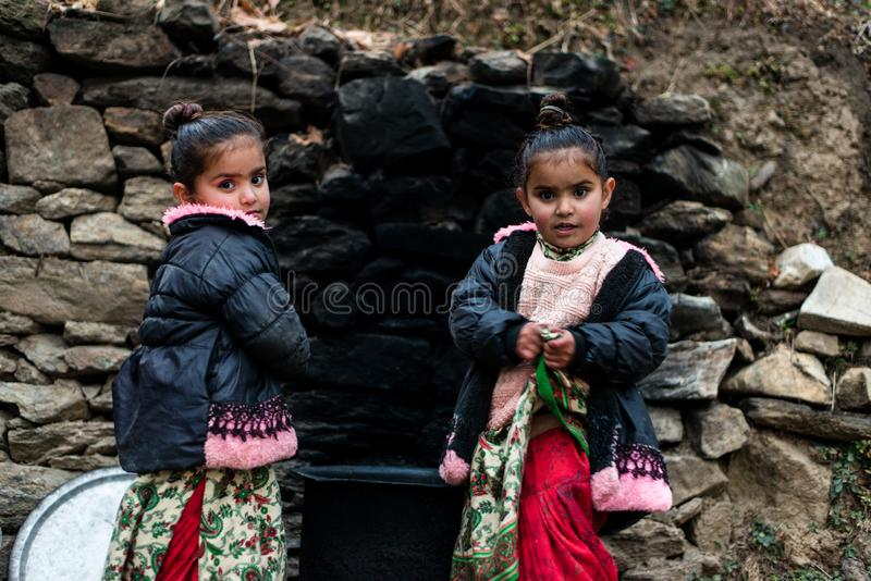 Kullu, Himachal Pradesh, India - December 21, 2018 : Photo of poor indian Twins girl child in mountains. Smile beautiful face female happy person portrait young stock images